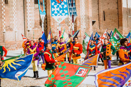 palio: Asti, Italy - September 16, 2012:: the historic Medieval Palio of Asti in Piedmont, Italy. Flag bearers in medieval historical costume at Palio Asti. Medieval historical parade with more than 2,000 people in period costume, parading in the city before the