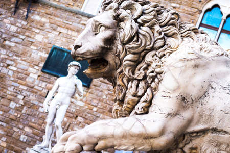 Lion at Loggia dei Lanzi and David by Michelangelo in front of Palazzo Vecchio Florence Italy