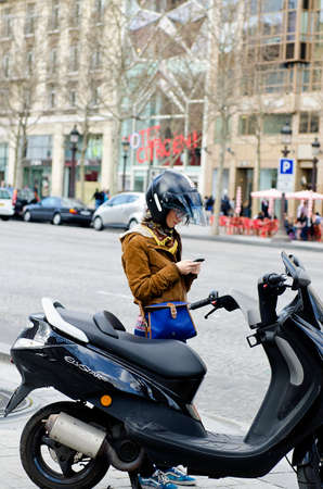 motor scooter: Paris, France - March 19, 2012: Young woman using her mobile phone before boarding the motor scooter in the Avenue des Champs-Elysees Paris. Editorial