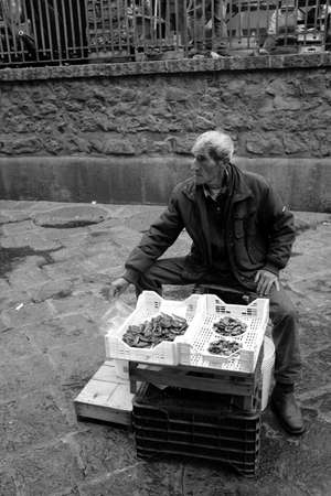 Catania, Italy - October 23, 2015: Fisherman sells fish and shellfish to the fish market. the historic fish market of Catania in Piazza Alonzo di Benedetto was created in 1814 by digging the embankment of the sixteenth-century walls, is today one of the t Editorial