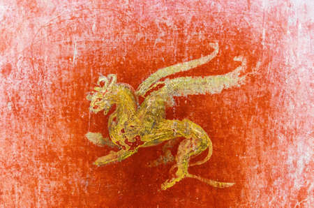 detail of the fresco in Pompeii with winged griffin on a red background Pompeian. Pompeii was destroyed, and completely buried, during a long catastrophic eruption of the volcano Vesuvius spanning in AD 79.