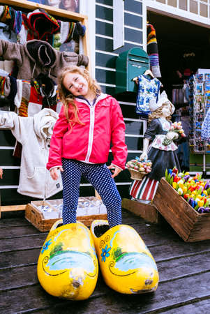 dutch girl: Little girl posing in typical huge Dutch wooden clogs front of a souvenir shop in Volendam, Netherlands