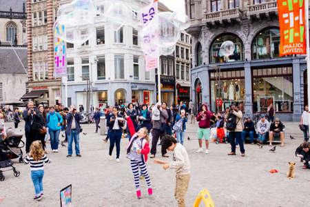 dam square: Amsterdam, Netherlands - June 16, 2016: Street artist making soap bubbles on the street in Dam Square in Amsterdam, Netherlands. Editorial