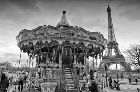 Paris, France - March 18, 2012: Children accompanied by their parents and grandparents play the carousel of the Eiffel Tower in Paris on a wet and cloudy day in March Editorial
