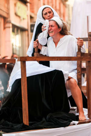 Asti, Italy - September 19, 2010: Historical representation of woman while giving birth during the historic parade of the Palio of Asti in Piedmont, Italy. The parade consists of more than 2000 dressed in medieval clothes. 新聞圖片