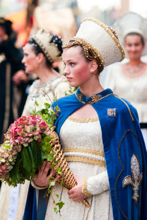 reenactment: Asti, Italy - September 19, 2010: Young Medieval Princess, during the historic parade of the Palio of Asti in Piedmont, Italy. Young damadel Middle Ages at the Palio with flowers Editorial