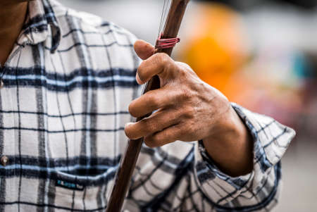man plays an erhu, two-stringed bowed fiddle. The Erhu is an ancient Asian instrument, brought to China 140 B.C. Stock Photo