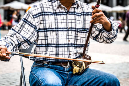 man plays an erhu, two-stringed bowed fiddle. The Erhu is an ancient Asian instrument, brought to China 140 B.C. Standard-Bild