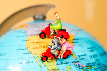 Travel Concept. miniature figures couple ride motorcycle