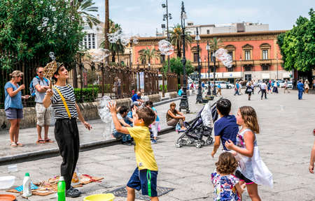 Palermo, Italy - April, 2018: Street artist making soap bubbles on the street in Piazza Giuseppe Verdi, in front of the opera house, Teatro Massimo.