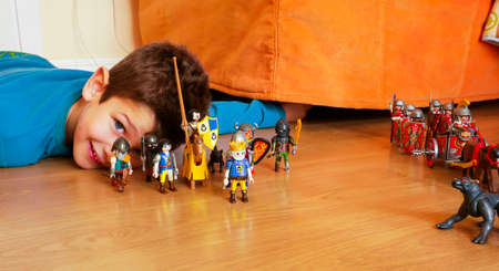 child lying on the floor of his room plays with the Playmobil warriors