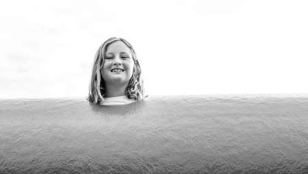little girl kick out her head out of the tunnel at the playground Archivio Fotografico