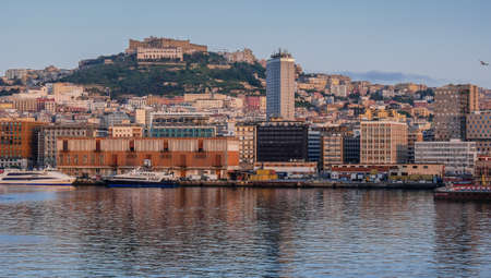 Naples April 2018 Italy: Port of Naples at dawn seen from the sea, urban landscape of the city of Naples with houses and buildings, view of the Castel Sant Elmo on the hill Editorial