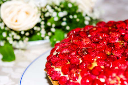 strawberry cake with flowers in the background