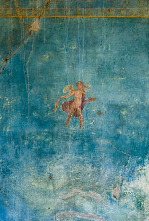 Amorino fresco on a wall with a blue background in a Domus of the ancient Pompeii destroyed by Vesuvius in 79 BC