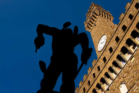 backlit of Perseus with the Head of Medusa 1545 of Benvenuto Cellini, with the Palazzo Vecchio in the background, Florence Stock Photo