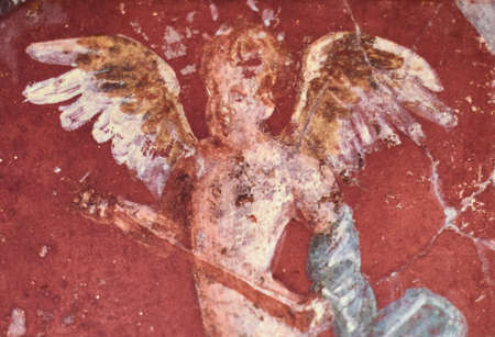 Fresco winged cupidon on red background in a Domus of the ancient Pompeii