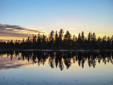 seclusion: Sunset behind forest by the lake Stock Photo