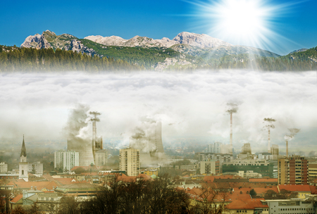 Town in smog with opposite mountains with sun