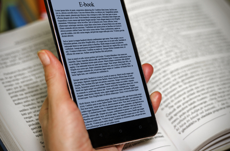 E-book on mobile device with real book in the back