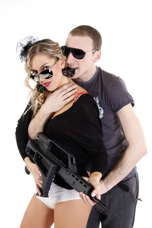 girl in sun glasses holding a weapon with a men behind  photo