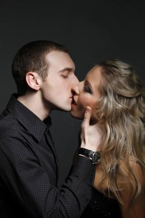 jovenes enamorados: apuesto hombre besa a una mujer hermosa Foto de archivo