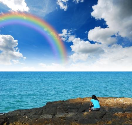 Alone vrouw op het strand wachten op iets hoop voor de toekomst en eenzaam meisje achtergrond ontwerp blauwe lucht, zee, zand zon regenboog Stockfoto