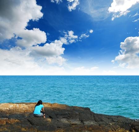 Alleen vrouw op het strand wachten op iets hoop voor de toekomst en eenzaam meisje achtergrond ontwerp blauwe lucht, zee, zand zon