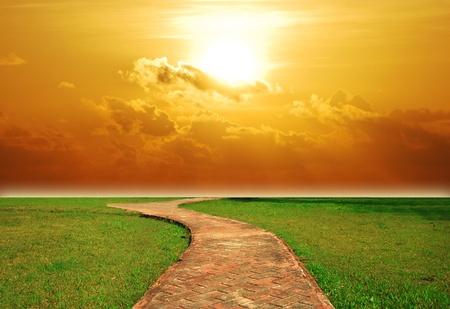 Zo achtergrond zonsondergang baksteen loopbrug zon bestemming gazon groen gras Stockfoto