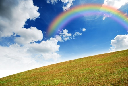 Green grass landscape blue sky for Backgrounds and design Yellow rainbow Foto de archivo