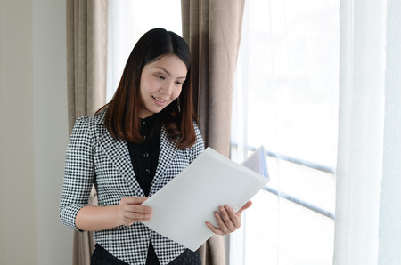 yuppie: young attractive woman with briefcase and checking document