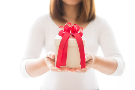 Gift box and red ribbon on hands of woman on white background Stock Photo