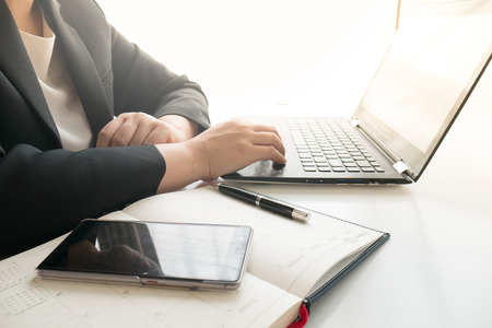 Businesswoman typing on laptop keyboard in office Stock Photo