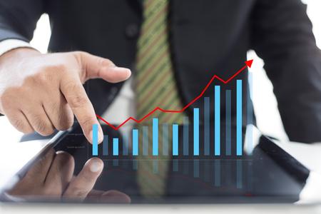 Van de de zakenmanhand van de de groeigrafiek de controlegrafiek op tablet, bedrijfsconcept