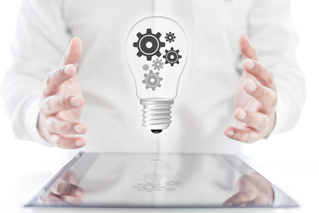 Businessman with graphic digital lamp of gear on tablet and hands , business concept