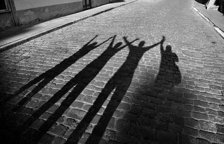 čtyři lidé: Čtyři stíny skočit na vozovce Reklamní fotografie