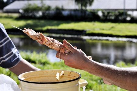 Man string raw meat on skewer  shish kebab