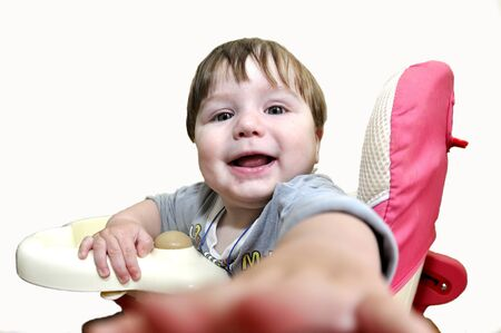baby on chair: Smile baby sit in baby chair and pulls hand on viewer