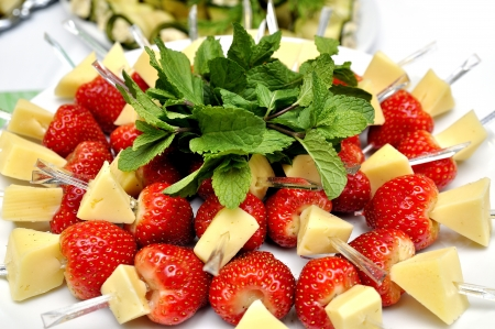 Canape with strawberry and cheese served with mint leaf