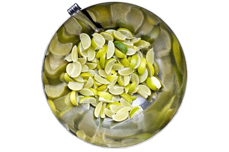 pincers: Sliced lime in metal bowl with pincers isolate