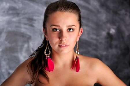 Young woman portrait with long red earrings Фото со стока