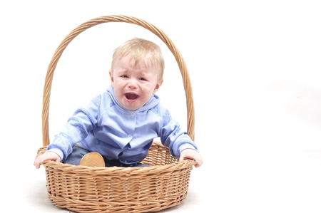 unfortunate: Baby boy crying in basket on white background
