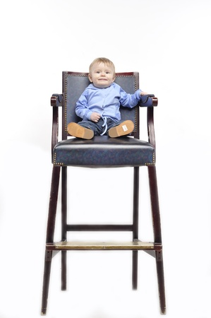 king chair: Kid sits in an old chair as the king
