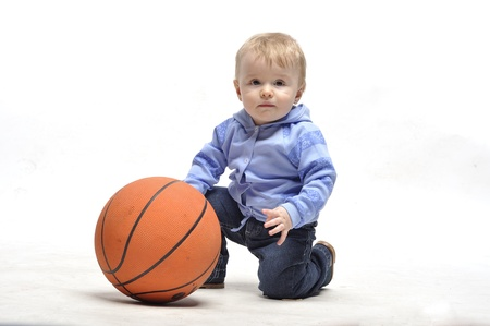 Little boy plays with basketball ball in studio