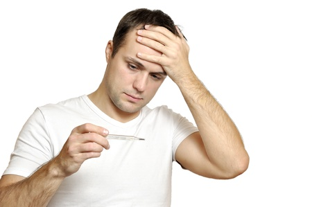 Sick young man looks at a thermometer photo