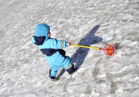 Le petit gar�on joue au terrain de jeu en hiver avec des jouets Banque d'images - 19537198