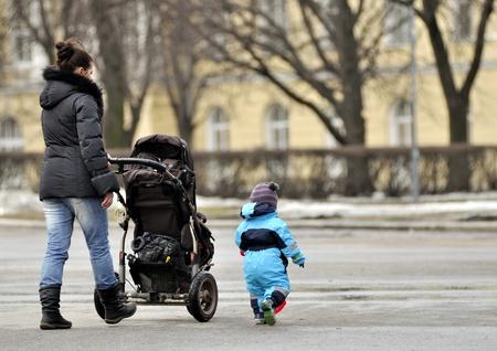 Mother with stroller walking near little son