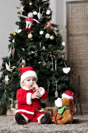 Baby in Santa costume sit near decorating Christmas tree with present toy Stock Photo - 22970323