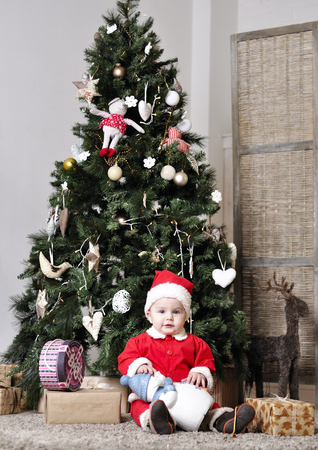 Baby in Santa costume sit near decorating Christmas tree with present toy photo
