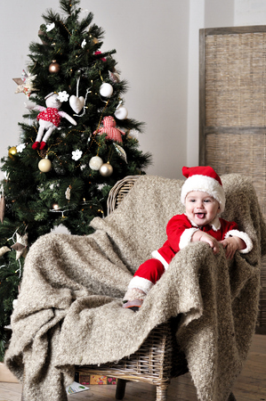 Baby in Santa costume sit on chair near Christmas tree Stock Photo - 22970332